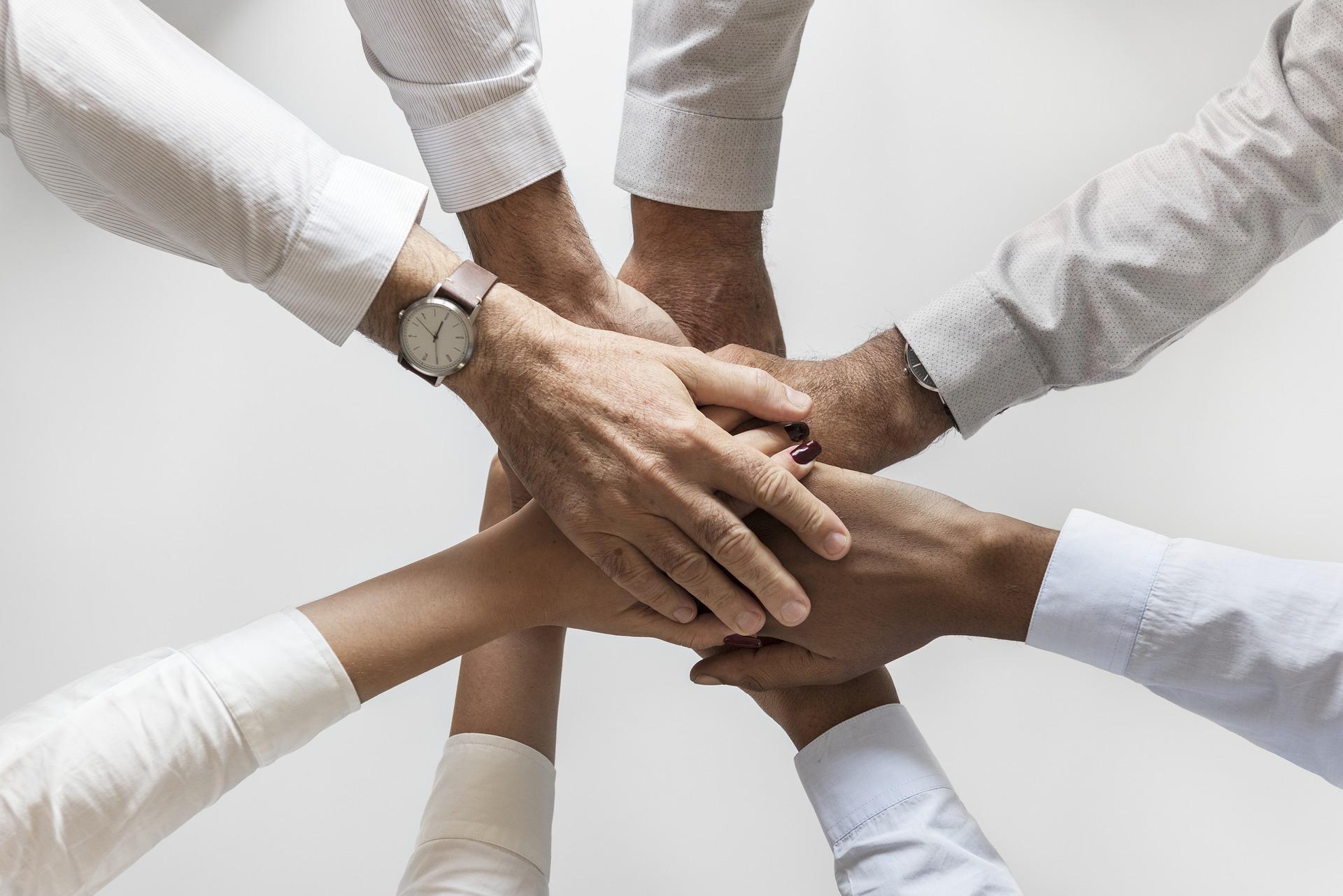 Monen ihmisen kädet päällekkäin