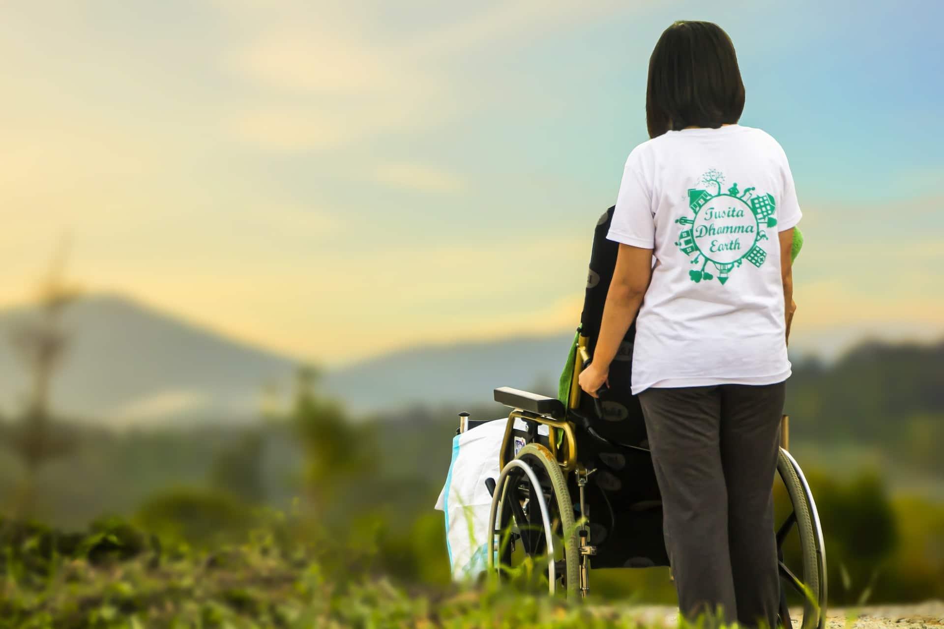 Hoitaja työntää asiakasta pyörätuolissa kauniin maiseman edessä