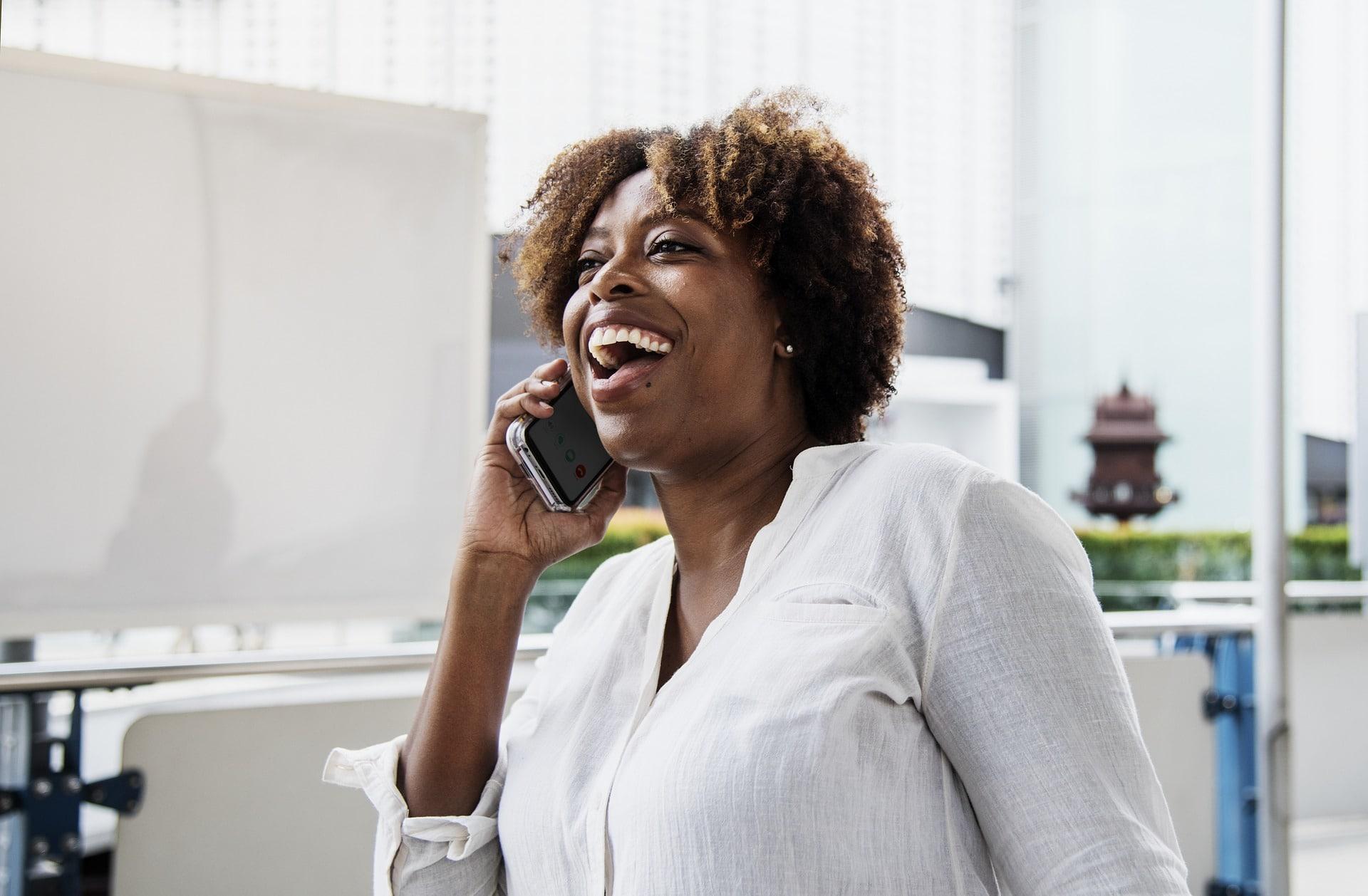 Iloinen nainen puhuu puhelimessa