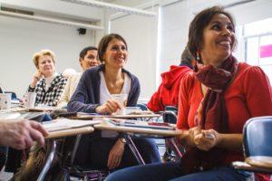 Iloisia ihmisiä opiskelemassa ja keskustelemassa yhdessä