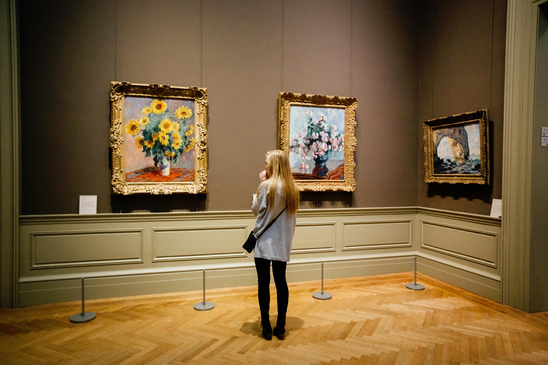 girl looking at paintings in museum
