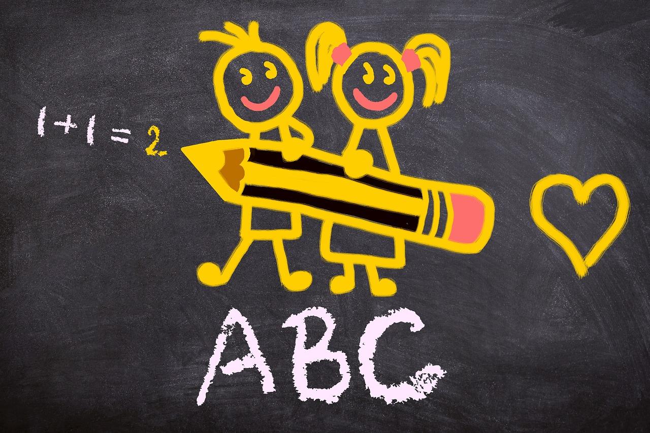 Liitutaululle piirrettyjä lapsihahmoja ja numeroita ja kirjaimia