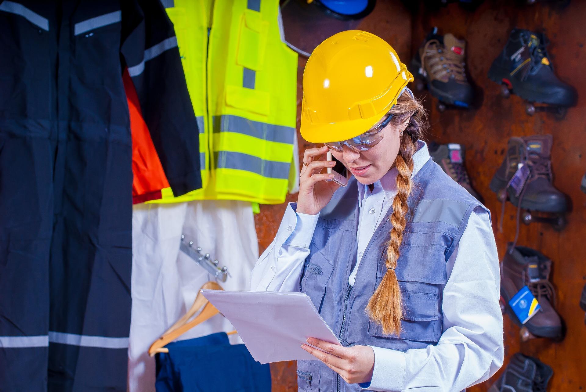 Työntekijä puhuu suojavarusteissa puhelimeen