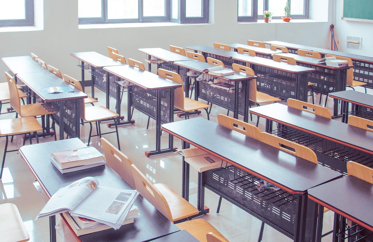 Luokkahuone jossa pulpetteja ja tuoleja