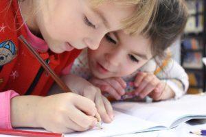 Kaksi lasta tekemässä läksyjä