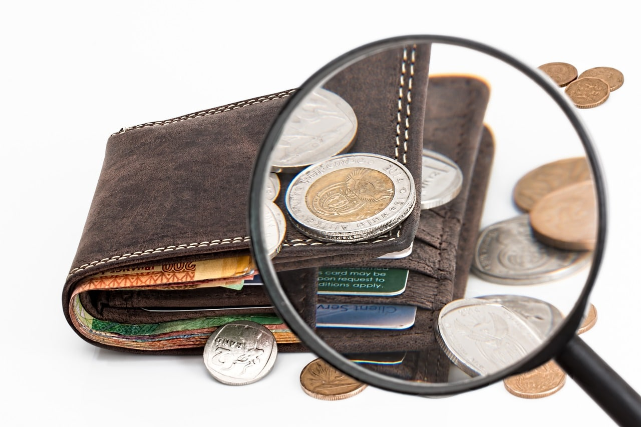 Wallet-with-money-under-magnifying-glass
