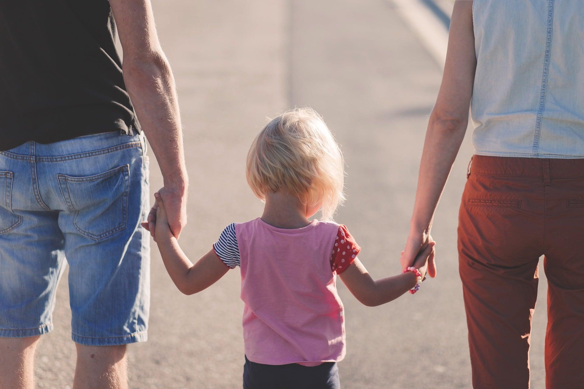 Lapsi pitää vanhempiaan kädestä