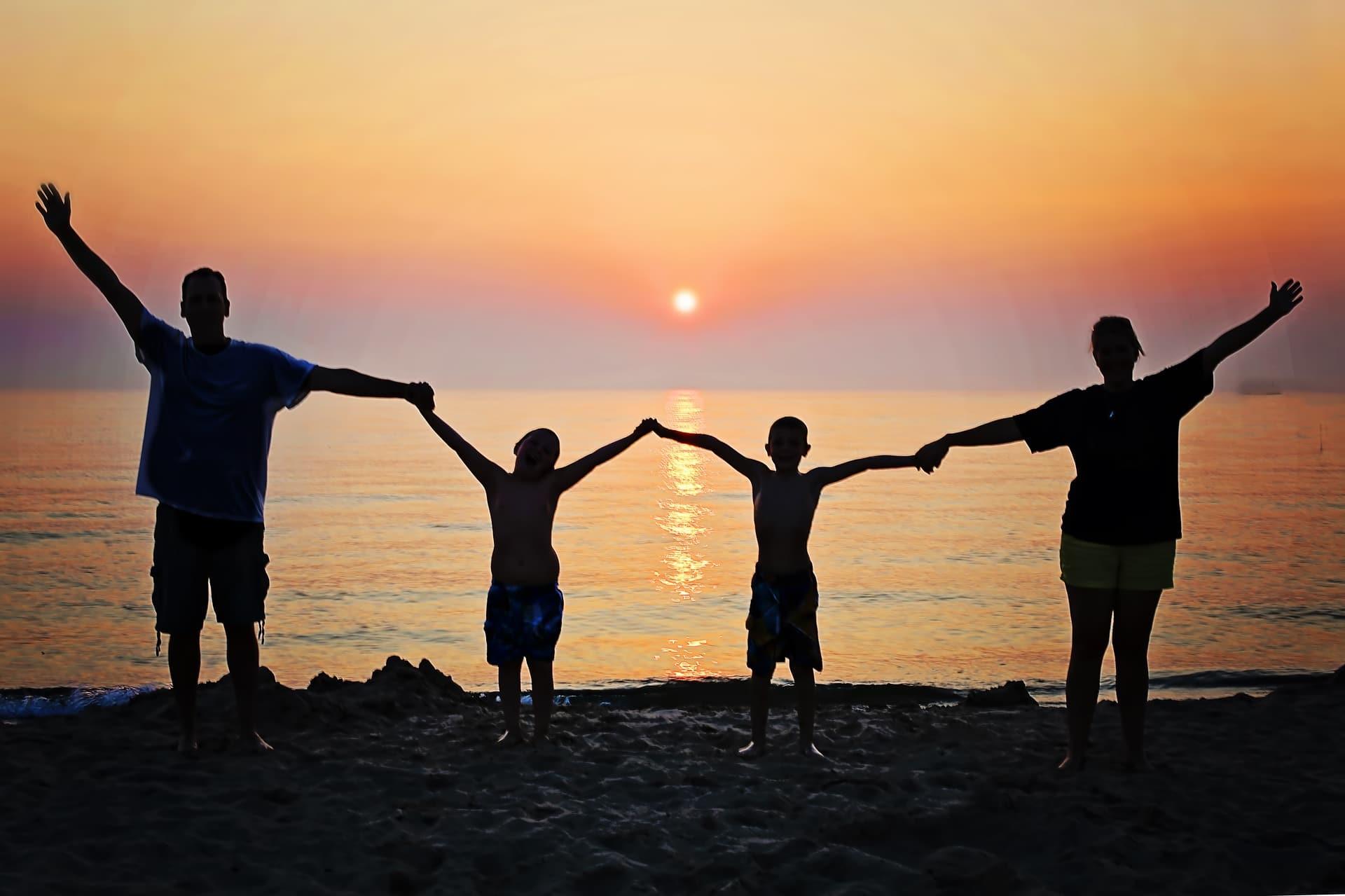 Perhe pitää toisiaan kädestä rannalla auringon laskiessa