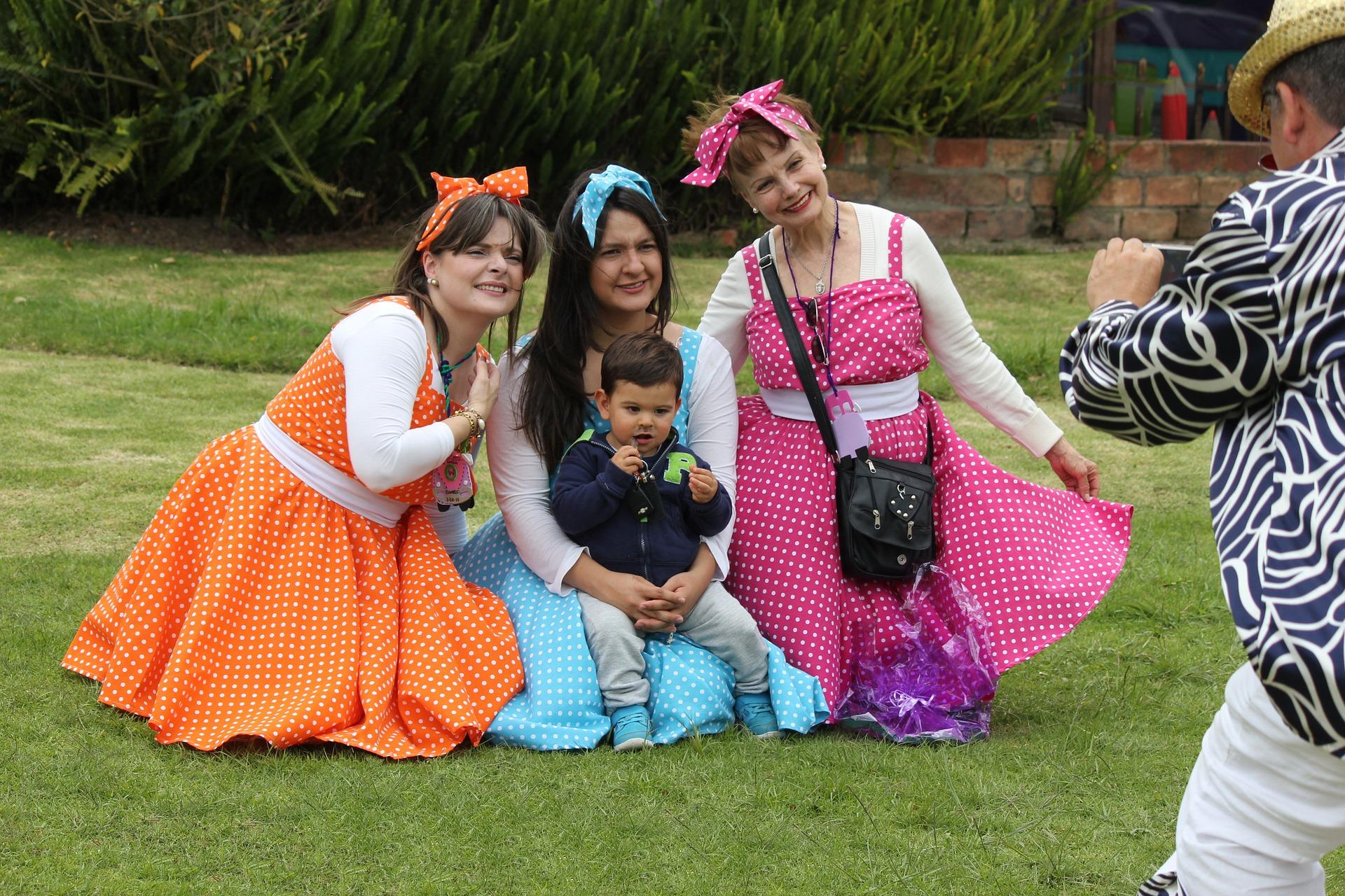في الصورة رجل يلتقط صورة لعائلة ترتدي ملابس حفلة