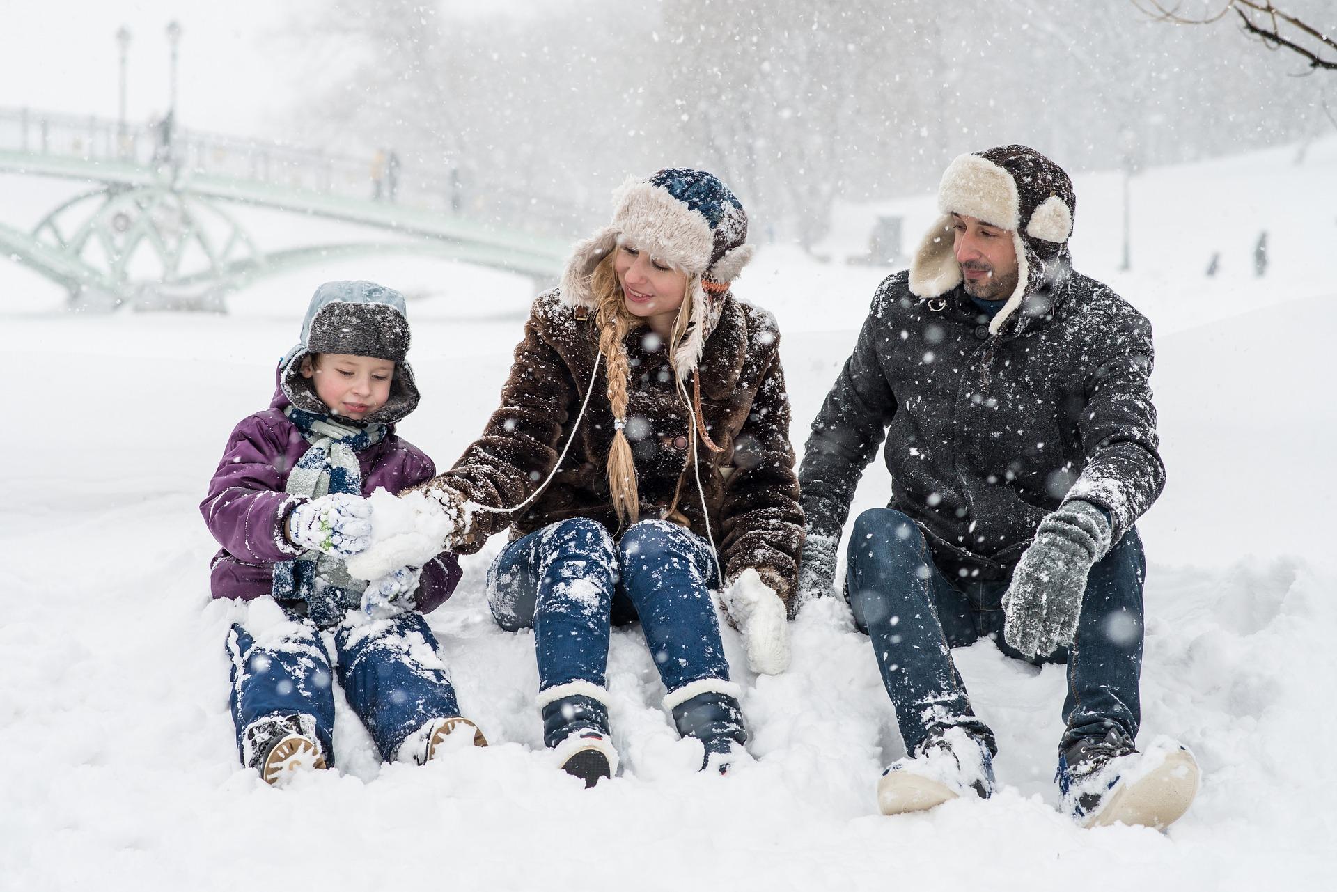 Lapsi ja vanhemmat istuvat lumihangessa