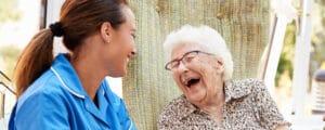 Vanhempi nainen istuu tuolilla ja puhuu sairaanhoitajan kanssa vanhainkodissa
