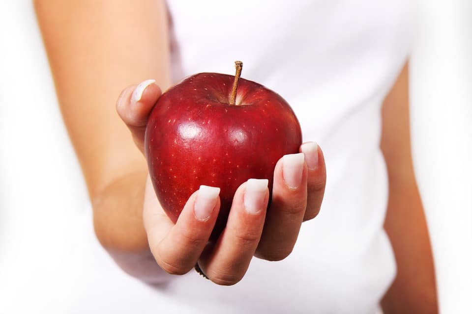 in picture a hand with an apple