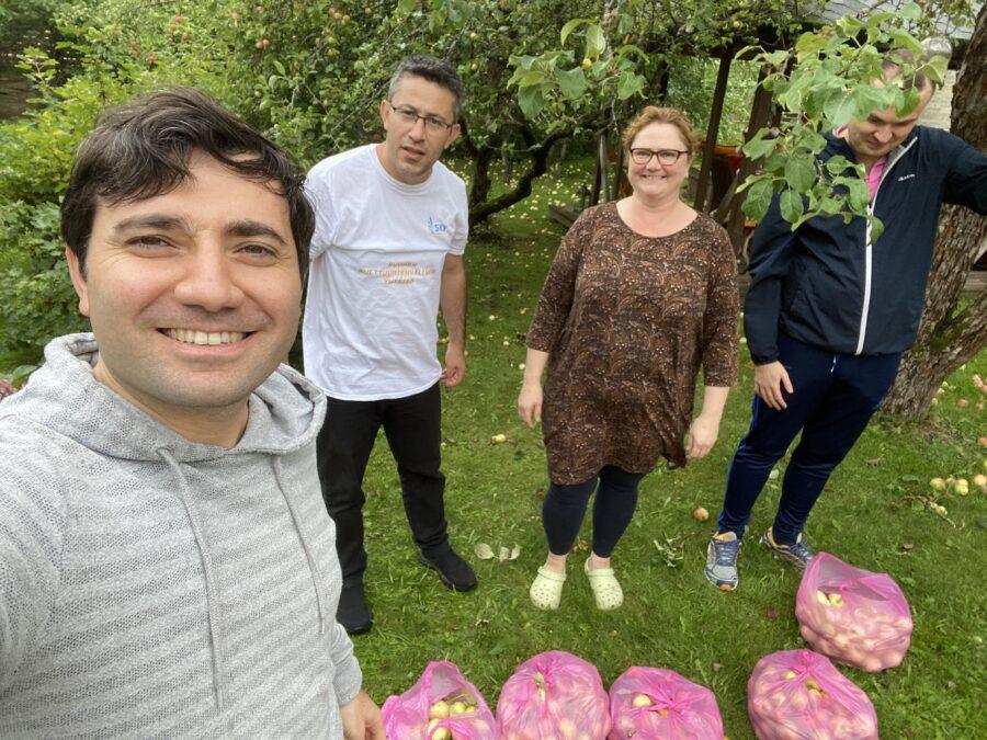 Ihmisiä omenapuutarhassa